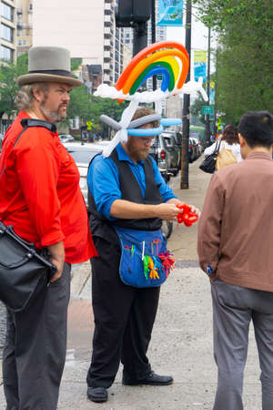 Chicago USA August 30 2015; Street performer making shapes out of colored balloons to entertain passers-by with a rainbow on his head and apron with stock of balloons.