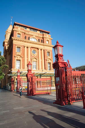 Auckland New Zealand - December 26 2015; Historic Ferry Building and red wrought iron fence and gates with long shadows on pavement