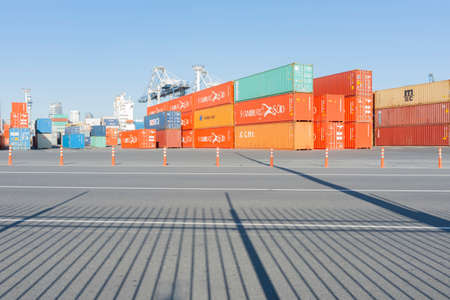 Auckland New Zealand - December 26 2015; Large waterfront yard of Ports Of Auckland with stacks of containers and port handling equipment beyond leading lines of fence shadows
