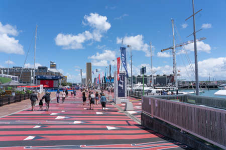 Auckland New Zealand- December 27 2020; People out enjoying summer on red and black painted pedestrian walkway along Auckland Wynyard Quarter waterfront 新聞圖片