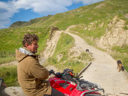 Tora, new Zealand - November 28 2011; New Zealand hill country farmer on quadbike with sheep dogs on track through hills.