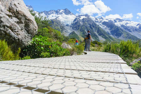 Mount Cook New Zealand - Febuary 16 2015; Tourists stop to look at view on wooden walkway on Hooker Valley Walk in South Island, New Zealand.