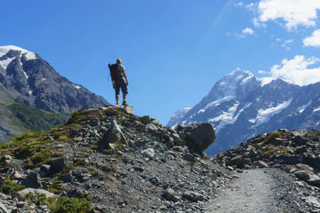Mount Cook New Zealand - February 16 2015; Lone Hiker stands on pile of rocks beside Hookers Valley Track looking to Mount Cook 新聞圖片