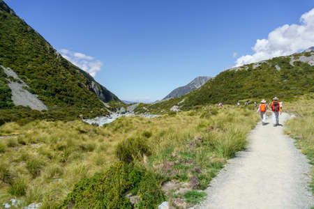 Mount Cook New Zealand - Febuary 16 2015; Hooker Valley track with tourists on one of great walks winding through alpine vegetation between mountain slopes with tourists enjoying the walk 新聞圖片