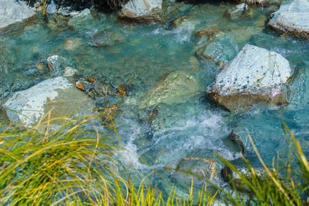 Cool water of Hooker River flowing over rocky river bed. in Mount Cook National Park.