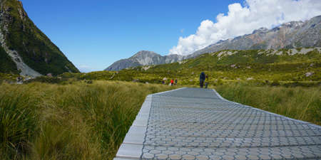 Wooden section of Hooker Valley walkway between mountains towards Mount Cook on sunny day. 新聞圖片