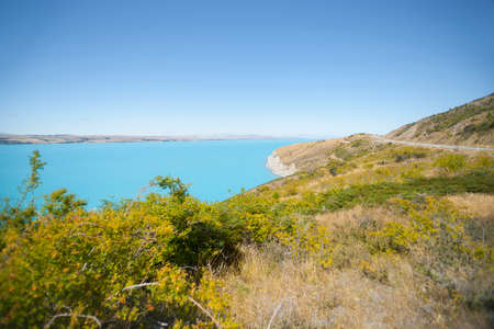 Turquoise blue water of snow feed scenic Lake Pukaki and highway around past lookout point Pete's Lookout by highway Canterbury New Zealand. 版權商用圖片
