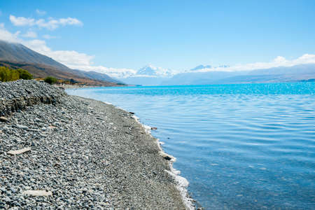 Mount Cook in distance at end of  turquoise blue water of snow feed scenic Lake Pukaiki in South Island New Zealand.