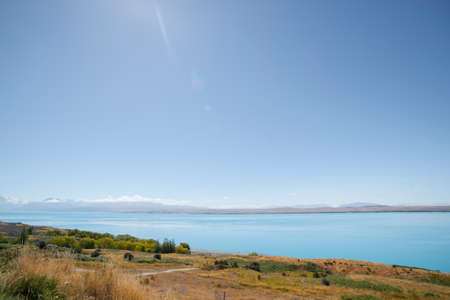 Lens flare in blue sky above golden and green slope leading to turquoise blue water of snow feed scenic Lake Pukaki from Pete's Lookout by highway Canterbury New Zealand.