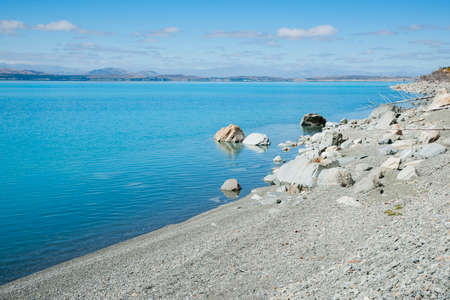 Grey stony lake edge and turquoise blue water of snow feed scenic Lake Pukaiki in South Ilsand New Zealand. 版權商用圖片