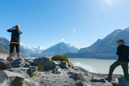 Mount Cook, New Zealand - February17 2015; Small group of tourists reach glacial lake in Southern Alps soon after sunrise.