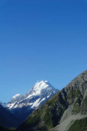 Snow-capped Mount Cook rises between slopes of Southern Alps under clear blue sky.