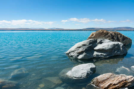 Large rocks on grey stony lake edge and turquoise blue water of snow feed scenic Lake Pukaiki in South Ilsand New Zealand.