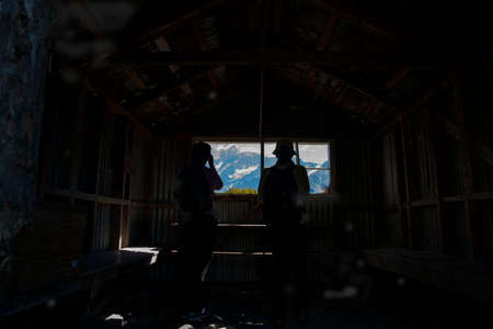 Trampers silhouetted as they look at mountain view through window of rustic and historic trampers hut in Mount Cook National Park, CAnterbury New Zealand.
