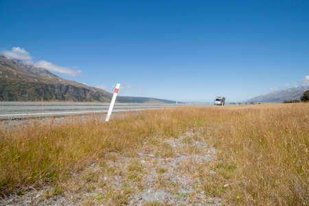 Camper van blurred as travels through landscape of golden grass from highway through Southern Alps In South Island New Zealand