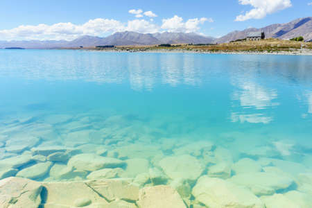 View across Tturquoise water of Lake Tekapo to distant otherside