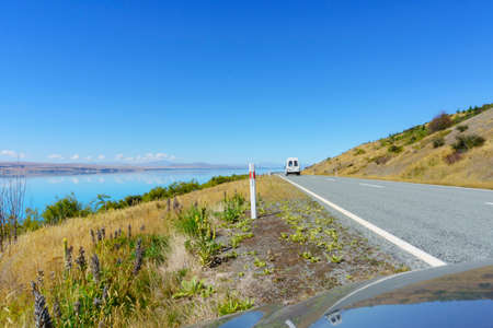 On highway around Lake Pukaki reflection in car bonnet of road ahead in view of turquoise water and blue sky.
