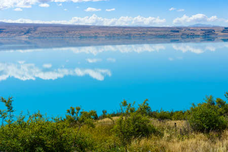 Turquoise blue water of Lake Pukaki with long white cloud reflections