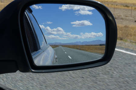 Road and rural scenery behind in rearvision mirror while traveling through rural South Island New Zealand. 版權商用圖片