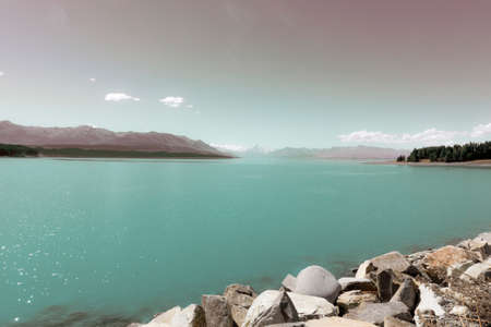 Vintage effect landscape beautiful Lake Tekapo with high sun and lens flare over turquoise water, rocky edge and surrounded by distant mountains and trees ion South Island New Zealand. 版權商用圖片