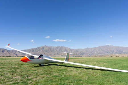 Omarama New Zealand - February 17 2015; Glider with bright orange nose resting on airfield surrounded by mountains of South Island