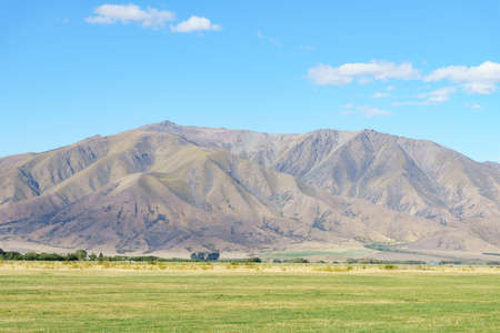 Mountain range background beyond field in Omarama New Zealand.1