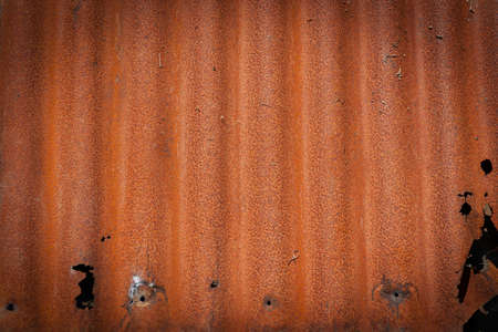 Rusty old corrugated sheet iron junk left on wall to rust away in close-up for background