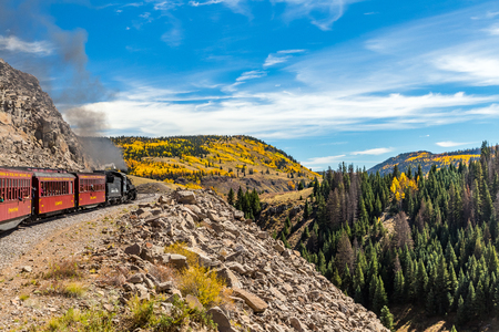 A Cumbres & Toltec steam locomotive pulls a passenger train along a rocky mountain ledge in the San Juan National Forest on a trip from Chama, New Mexico through a beautiful scenic route ending in Antonito, Colorado Editorial
