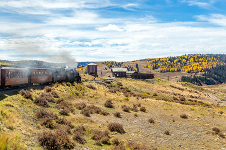 A Cumbres & Toltec steam locomotive arrives at Osier Station with a passenger train traveling through the San Juan National Forest on a trip from Chama, New Mexico through a beautiful scenic mountain route ending in Antonito, Colorado
