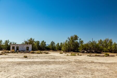 An abandoned building sits alongside the roadway near Death Valley Junction in the Funeral Mountains Wilderness Area, California. Stock Photo