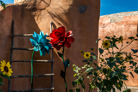A kiva ladder and a mixture of real and artificial flowers decorate an wall in Old Town, Albuquerque, New Mexico. Stock Photo