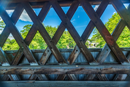 pedestrian bridge: The Henniker Covered Bridge is a covered pedestrian footbridge serving New England College across the Contoocook River in Henniker, New Hampshire. Stock Photo