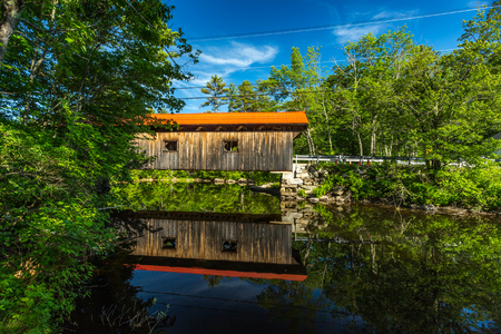 The Covered Bridge carries Newmarket Road over the Warner River near the Falls in Warner, New Hampshire. The Town lattice truss bridge was built in 1859-60.