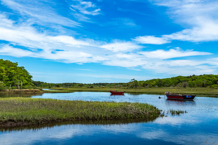 Two boats lay at anchor on the Herring River at Harwich, Massachusetts on Cape Cod.