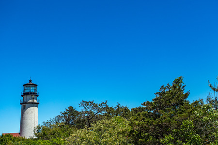 The Highland Light at Truro on Cape Cod stands out against a clear bue sky.