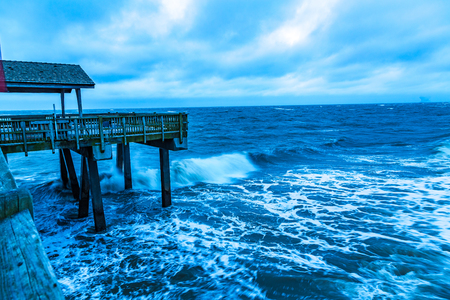 A stormy morning crashes ocean waves against the pier at Tybee Island, Georgia.
