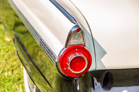 A taillight on the rear of a vintage automobile.