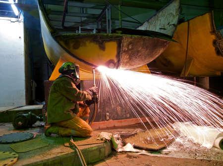 A workman flame cutting a lage metal tank