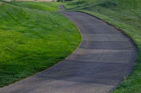 A winding cart path down a set a green rolling hills.