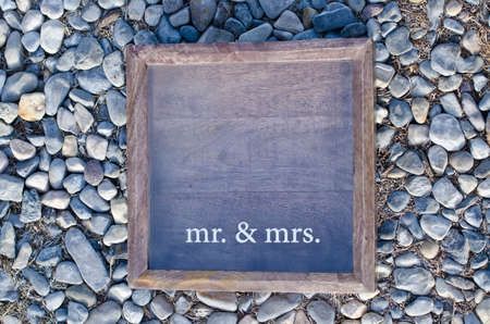 A closeup of a wooden wedding photo frame on a pebble background.