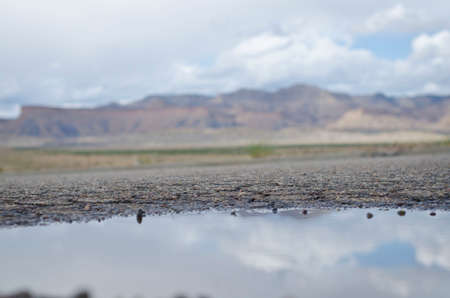 A cool cam view of the mountain range in the open road rain puddle of the summer storm.