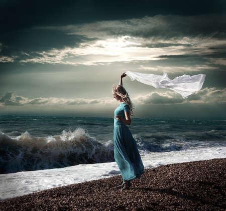 scarf beach: Foto oscura de mujer rubia con bufanda blanca en Mar Tormentoso