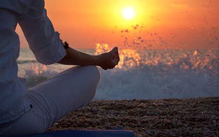Kobieta praktykowania jogi w pobliżu oceanu o zachodzie słońca Zdjęcie Seryjne