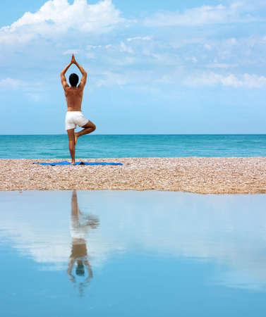 Man Practicing Yoga near the Sea and Reflected on Water Stock Photo