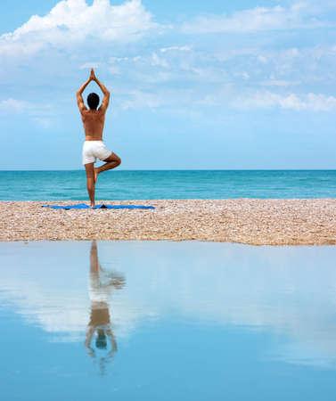 Man Praticare Yoga in prossimità del mare e riflessa sull'acqua