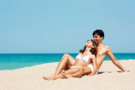 Happy Young Couple Lying on a Beach and Holding Each Other photo