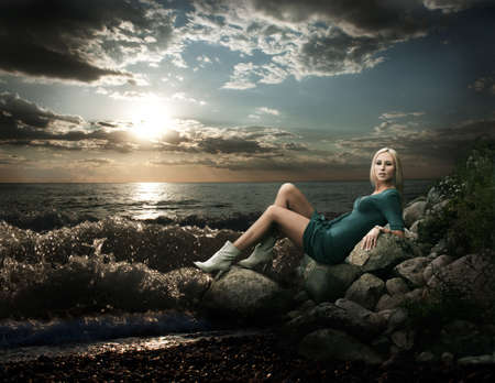 Fashion Photo of Blonde Woman on the Rock near the Stormy Sea