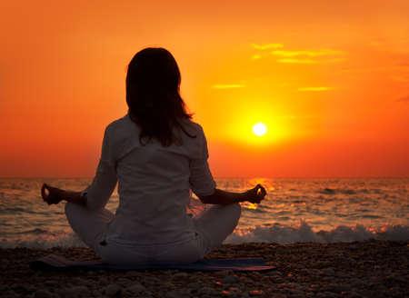 mujer meditando: Mujer que practica yoga cerca del mar al atardecer Foto de archivo