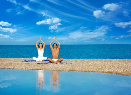 mujer meditando: Joven Mujer y Hombre haciendo yoga en el mar y reflejada en el agua Foto de archivo