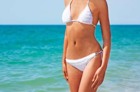 flat stomach: Bella donna in bikini in piedi in mare